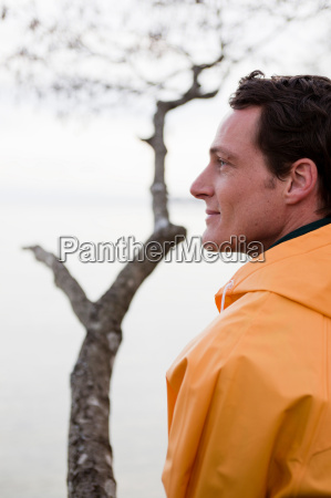 man in raincoat looking on a