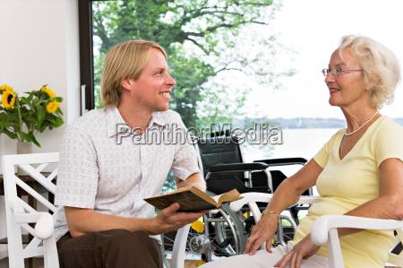 man reading book to senior woman