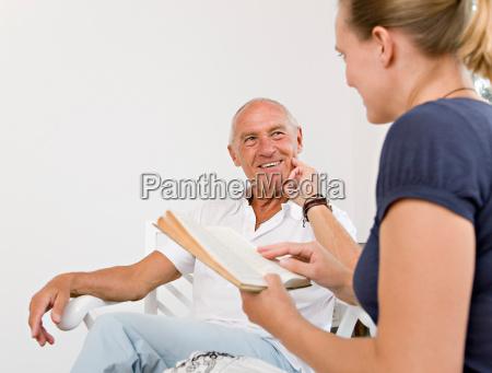 woman reading book to senior man