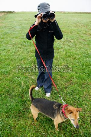 girl with binoculars walking the dog