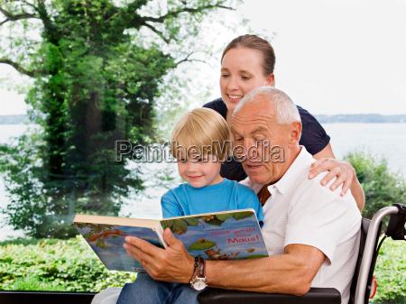 senior man reading book to boy
