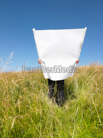 man with blueprints in field