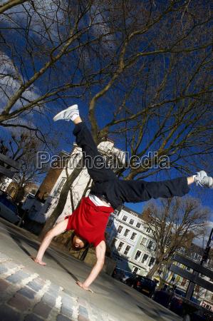 man doing handstand in street