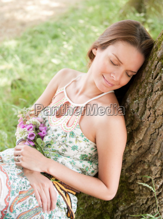 woman lying against tree