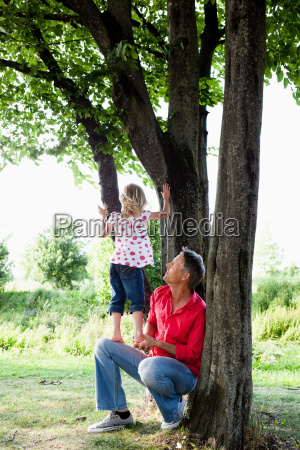 father and daughter climbing on tree