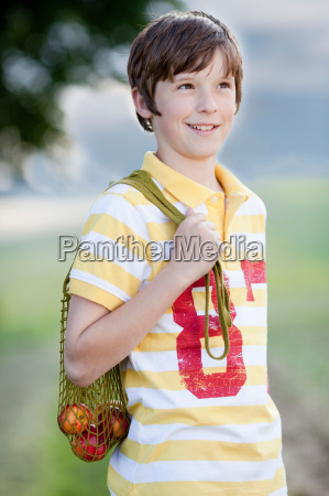 young boy carrying a net of