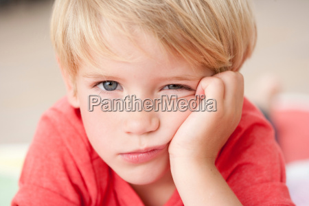 young boy looking bored at viewer