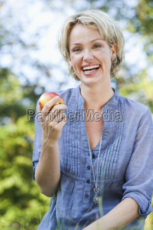 woman smiling holding apple