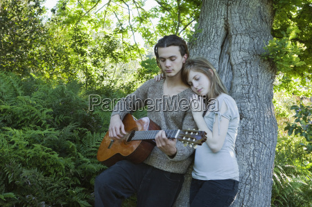 young man with girl playing guitar