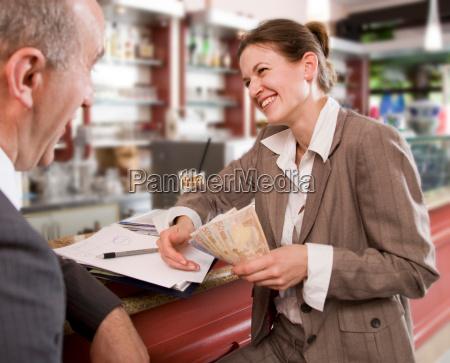 businesswoman paying man in bar