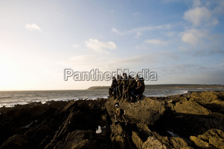 group of friends sitting on rock