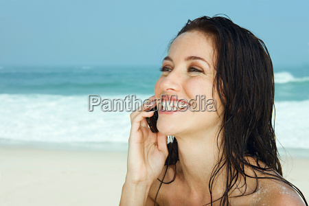 women with mobile phone on beach