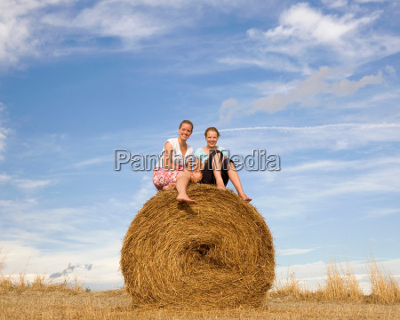girl and woman sitting on hay