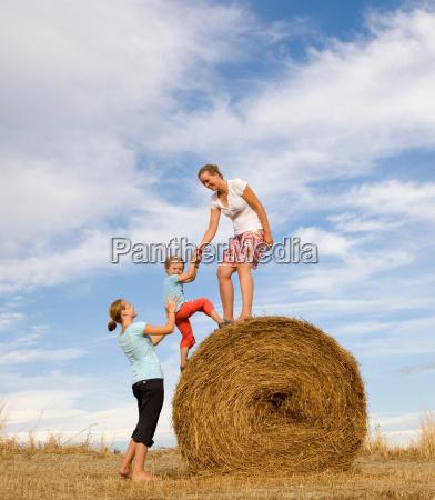 girl woman help boy to climb