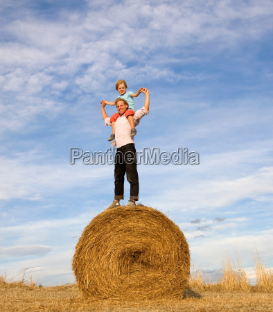 man and boy standing on hay