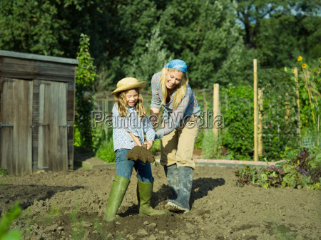 a woman and girl digging a