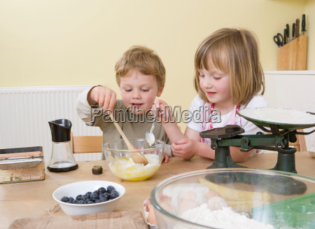 boy and girl making fruit muffins