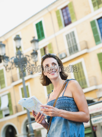 woman holding map looking around