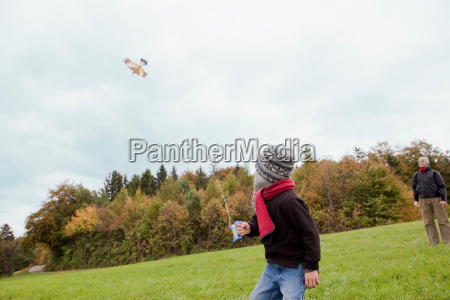 father watching son flying a kite