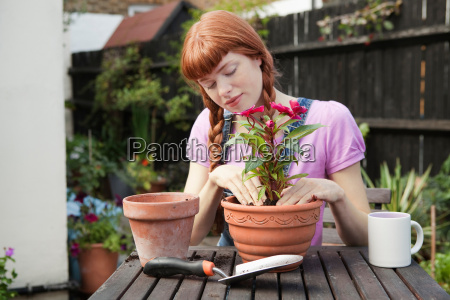 woman repotting plant sitting in garden