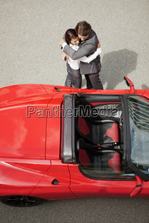 business couple huging near electric car