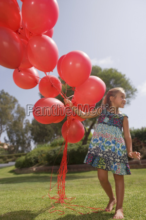 young girl holding bunch of red