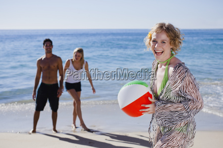 woman carrying ball on beach