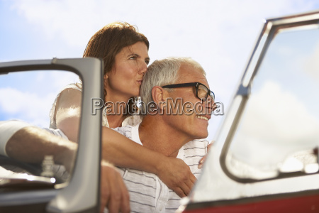 senior couple embracing in sports car