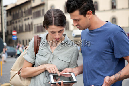 young couple using digital tablet florence