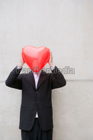 man in suit holding a heart