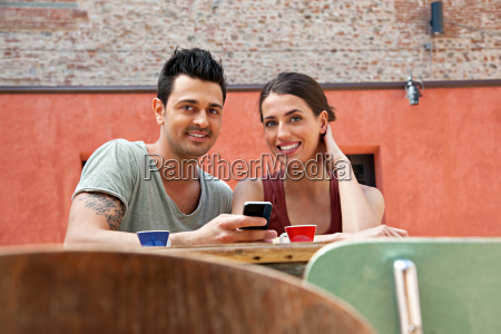 couple with smartphone outside cafe florence