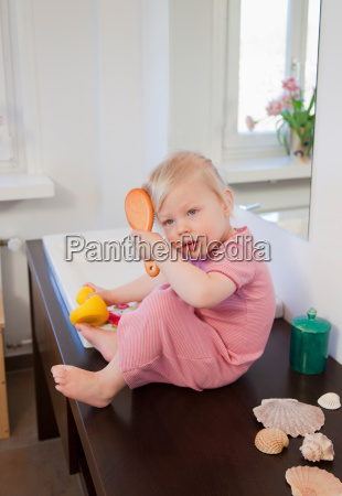 toddler girl brushing her hair