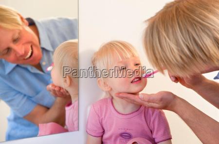 father brushing toddler daughters teeth