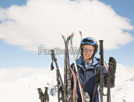 boy with skis in mountain scene