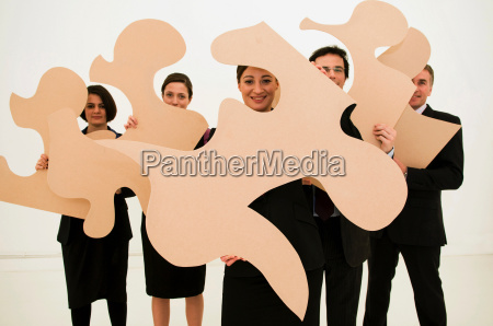 group of business people hold jigsaw