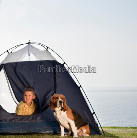boy with dog in tent by