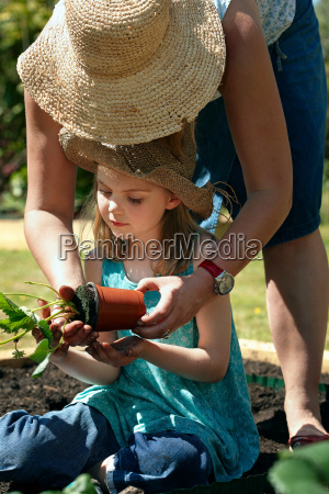 mother and daughter planting plants
