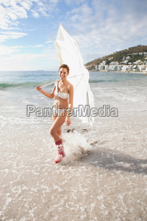 woman carrying umbrella on beach