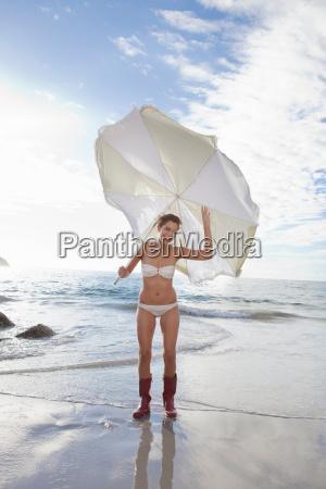 woman carrying umbrella on beach