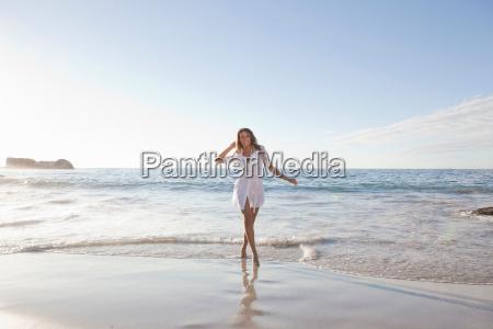 woman walking in surf on beach