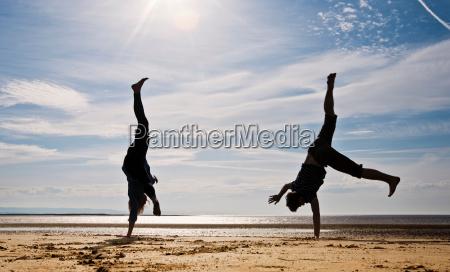 two people cartwheeling on beach