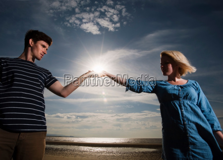 couple on beach holding sun in