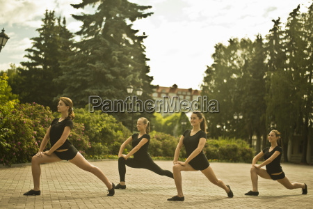 four young ballet dancers exercising in
