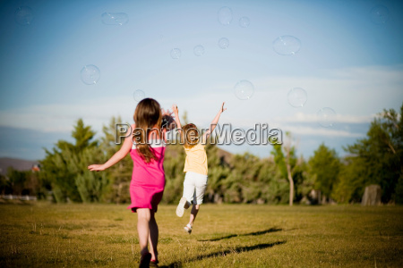 2 young girls chasing bubbles in