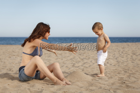 pregnant woman sitting on beach with