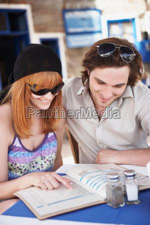 young couple looking at menu