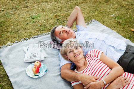 couple laying on picnicblanket in grass