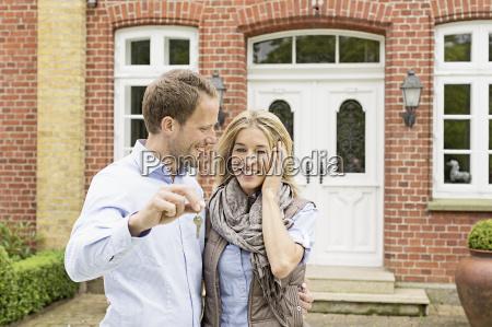 mid adult couple outside house man