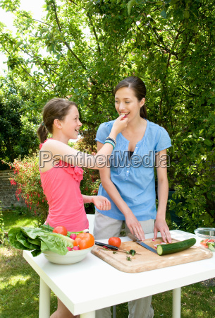 daughter feeds mother salad outdoors