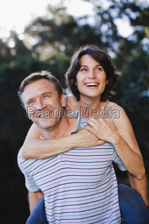 man carrying woman piggyback outdoors